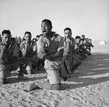606f0e4e0 A squad of men kneel in the desert sand while performing a war dance. Māori  Battalion haka ...